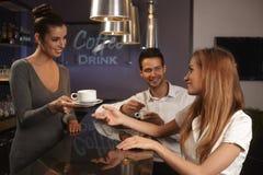 Barman féminin servant de jeunes couples dans la barre Photos stock