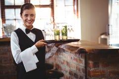 Barman féminin tenant un plateau de portion avec deux verres de cocktail photographie stock
