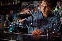 Barman féminin versant un cocktail alcoolique brun de la tasse de mesure au verre photographie stock libre de droits