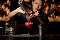 Barman féminin versant un cocktail avec le dispositif trembleur et le tamis image libre de droits