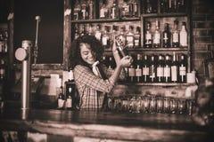 Barman fêmea que mistura uma bebida do cocktail no abanador de cocktail fotos de stock