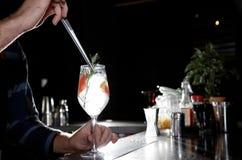 Barman faisant à genièvre de pamplemousse le cocktail tonique au compteur dans le bar image libre de droits