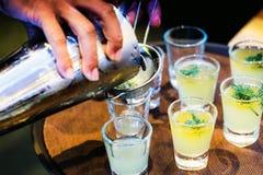 Barman faisant le cocktail d'alcool au compteur de barre, à la vodka de cocktail ou au genièvre photo stock