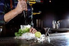 Barman faisant le cocktail de Mojito au compteur dans le bar, plan rapproché images stock