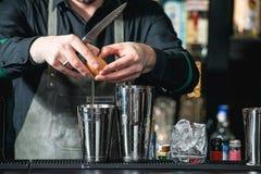 Barman faisant le coctail de détente sur un fond de barre Photos stock