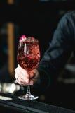 Barman faisant le coctail rose régénérateur avec une rose sur l'isolant de dessus photos stock