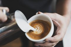 Barman faisant le latte ou l'art de cappuccino avec la mousse écumeuse, tasse de café en café photo libre de droits