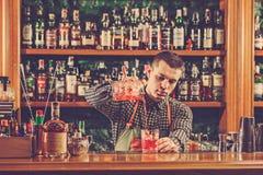 Barman faisant un cocktail alcoolique au compteur de barre sur le fond de barre photo stock