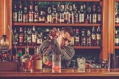 Barman faisant un cocktail alcoolique au compteur de barre sur le fond de barre Image libre de droits