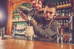 Barman faisant un cocktail alcoolique au compteur de barre sur le fond de barre Images libres de droits