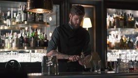Barman farpado alto que esmaga a parte grande de gelo com a posição da faca no contador da barra Empregado de bar que faz o cockt filme