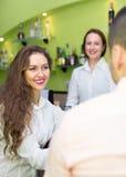 Barman femelle et deux clients en café Photo stock