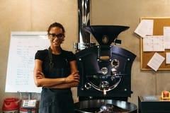 Barman femelle se tenant près de la machine de torréfaction de café dans le café photos libres de droits