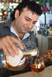 Barman fills glass. Royalty Free Stock Image