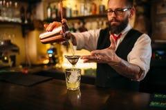 Barman flaring behind bar counter Royalty Free Stock Photo
