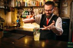 Barman flaring behind bar counter Stock Photos