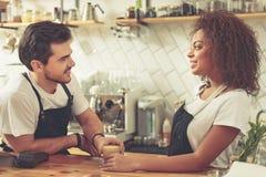 Barman gais communiquant pendant leur travail en café confortable image stock