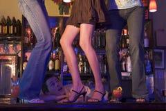 Barman gapend bij drie jonge vrouwen die op staaf dansen Stock Afbeelding