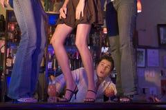 Barman gaping at three young women dancing on bar. Barman looking up at three young women dancing on bar Royalty Free Stock Images