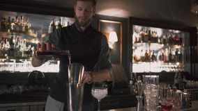 Barman gietende alcohol in beker toen in glas met ijs, die zijn vaardigheden aantonen Barman die cocktail in modern maken stock footage