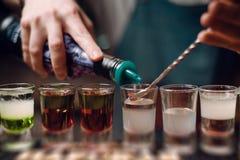 Barman gietende schoten bij een barteller de barmanhanden werken dicht uit stock afbeeldingen