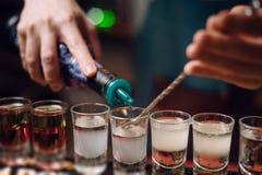 Barman gietende schoten bij een barteller de barmanhanden werken dicht uit royalty-vrije stock afbeelding