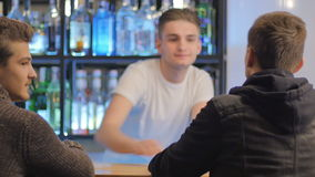 The barman greets with two attractive men who sit at the bar. Shooting from the back of two men. Two guys sits on a bar and talks with each other. The barman stock video footage