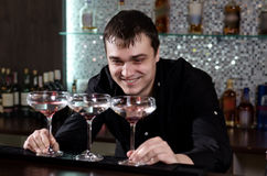 Barman grinning as he plays with three cocktails Royalty Free Stock Images