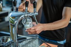Barman hand at beer tap pouring a draught beer royalty free stock photos
