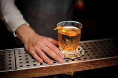 Barman hand with a glass of fresh old fashioned cocktail with orange peel royalty free stock photos