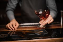 Barman hand holding a glass of red decorated alcoholic drink stock images