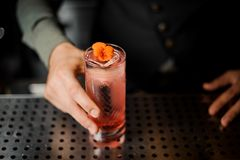Barman hand holding a glass with summer light sour cocktail with pink peach liquor decorated with flower. Under the bar counter Royalty Free Stock Images