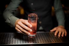 Barman hand holding a glass with summer light sour cocktail with pink peach liquor. Under the bar counter Stock Images