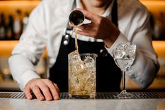Barman hand pouring a portion of alcoholic drink into a glass Stock Images