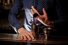 Barman hand pouring a portion of pink alcohol drink into the shaker. For making fresh summer cocktail stock image