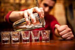Barman hand with shake mixer pouring beverage into glasses Royalty Free Stock Photography