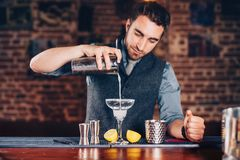barman hands adding ice and tequila to modern urban cocktails. Sky bar serving elegant drinks royalty free stock images