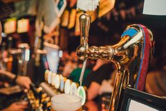 Barman hands pouring a lager beer in a glass. royalty free stock photos