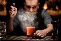 Barman het bespuiten aan het cocktailglas met één groot ijsblokje onder het licht royalty-vrije stock afbeeldingen