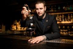 Barman het dalen ijsblokje in alcoholcocktail stock fotografie