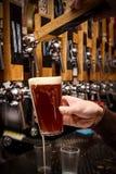 Barman het gieten van kraan vers bier in het glas in bar royalty-vrije stock afbeeldingen