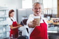 Barman heureux donnant la tasse à emporter images libres de droits