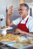 Barman heureux faisant des gestes le signe correct derrière le compteur photo libre de droits