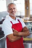 Barman heureux souriant à l'appareil-photo avec des bras croisés image stock