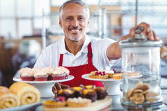 Barman heureux souriant à l'appareil-photo derrière des plats des gâteaux Image libre de droits