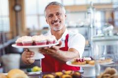Barman heureux souriant à l'appareil-photo et tenant un plat des petits gâteaux image libre de droits