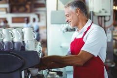 Barman heureux utilisant la machine de café image libre de droits