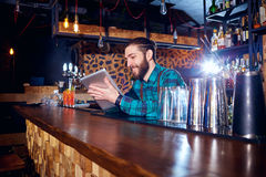 Barman with a hipster beard looks at  laptop behind  counter in. The bar Stock Photography