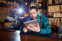 Barman with a hipster beard looks at  laptop behind  counter in Royalty Free Stock Photography