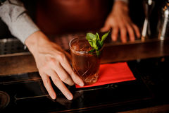 Barman holds a cocktail with mint in his hand. No face Royalty Free Stock Photography